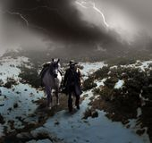 Cowboy under the storm. Cowboy and his horse, under lightnings at the beggining of the spring, into a snowy and windy landscape of forests and mountains Royalty Free Stock Photography