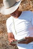 Cowboy using tablet computer Royalty Free Stock Photo