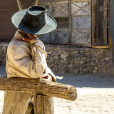 Cowboy waiting in the sun. People photo: Cowboy with hat waiting leaned against the railing in the heat of the desert stock images