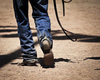 Cowboy Walking. Cowboy with spurs walking on a dirt road royalty free stock images