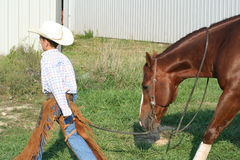 Cowboy walking horse. A small boy dressed up like a cowboy walking his brown horse in the grass royalty free stock photos
