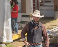 Cowboy walks into arena to compete in Wild Horse Race at stampede. Williams Lake, British Columbia/Canada - July 2, 2016: cowboy walks toward arena to compete in Royalty Free Stock Photo