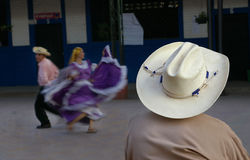 Cowboy watching hispanic dancers Royalty Free Stock Photos