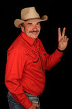 Cowboy waving. A studio portrait of a man in a red cowboy shirt and hat, turning to wave with two fingers upraised.  Model looks like Burt Reynolds.  Black Stock Images