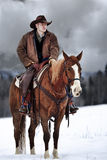 The Cowboy Way. Cowboy in Northern Montana looking over horse herd in the snowy mountains Stock Images