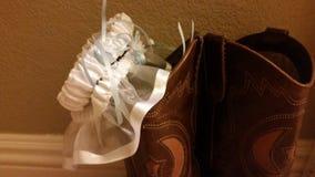 Cowboy wedding. Garter on cowboy boots stock photo