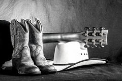 Cowboy Western Scene. A western arrangement with cowboy boots, hat and an acoustic guitar Stock Images