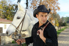 Cowboy with white horse and handgun Royalty Free Stock Photos