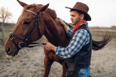 Cowboy wirft mit Pferd auf Texas-Ranch, wilder Westen auf stockfotos
