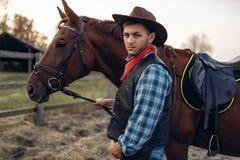 Cowboy wirft mit Pferd auf Texas-Ranch, wilder Westen auf stockfoto