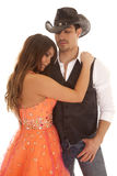 Cowboy woman orange dress her lean on his chest Royalty Free Stock Photos