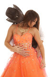 Cowboy woman orange dress look down. A cowboy leaning in to kiss his woman's neck Stock Photo