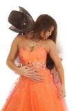 Cowboy woman orange dress look down Stock Photo