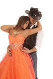 Cowboy woman orange dress reach back to neck. A cowboy holding on to his beautiful women in her formal dress Royalty Free Stock Photo