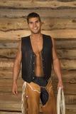 Cowboy wood behind black vest hold rope look Royalty Free Stock Image