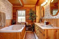 Cowboy wood cabin bathroom with tub. WOod cabin bathroom with tub and wallpaper stock photos