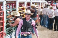 Cowboyen ler för press, som han går vid banorna på Williams Lake Stampede arkivbild