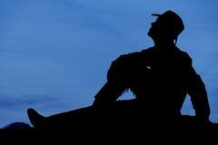 Cowboyen sitter solnedgång ser upp Royaltyfria Bilder