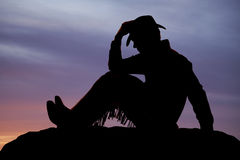Cowboyen sitter solnedgånghållhatten Arkivbilder