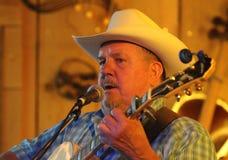 Cowboyen spelar gitarren och sjunger Arkivfoto