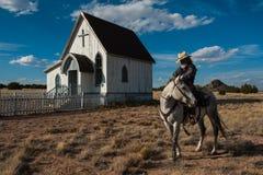 Cowboyen vilar hans häst framme av en gammal kyrka i landsbygd av nytt - Mexiko Royaltyfri Fotografi
