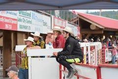 Cowboyer sitter på staket- och klockaloppet på Williams Lake Stampede royaltyfri bild