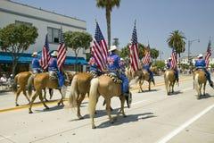 Cowboyer som marscherar med amerikanska flaggan som visas under invigningsdag, ståtar ner State Street, Santa Barbara, CA, gamla  Arkivfoto
