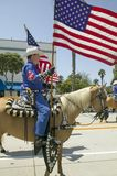 Cowboyer som marscherar med amerikanska flaggan som visas under invigningsdag, ståtar ner State Street, Santa Barbara, CA, gamla  Arkivbild