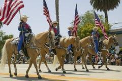 Cowboyer som marscherar med amerikanska flaggan som visas under invigningsdag, ståtar ner State Street, Santa Barbara, CA, gamla  Arkivbilder