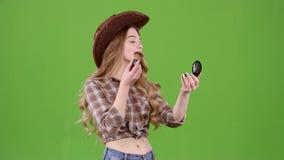 Cowboyflickan rymmer en borste och pudrar hennes framsida grön skärm stock video
