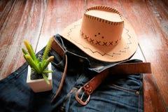 Cowboyhatt och jeans och bälte och kaktus arkivfoton
