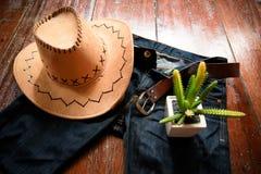 Cowboyhatt och jeans och bälte och kaktus arkivbilder