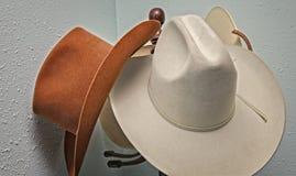 Cowboyhattar som hänger på en hattkugge Arkivbild
