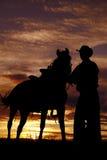 Cowboyholdingpferd im Sonnenuntergang Lizenzfreie Stockfotografie