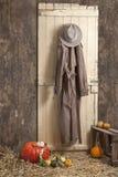 Cowboyhut und Mantel, die auf einem Barndoor haning sind, lizenzfreie stockfotografie