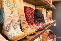 Cowboykängor på en hylla i ett lager som arrangera i rak linje arkivbilder