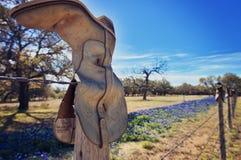 Cowboykängor på försett med en hulling - trådstaket med bluebonnets Arkivbild