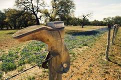 Cowboykängor på försett med en hulling - trådstaket med bluebonnets Arkivfoto