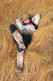 Cowboymädchen, das auf einem Gebiet des Grases liegt Lizenzfreies Stockbild