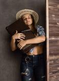 Cowboymädchen oder hübsche Frau im stilvollen Hut und blauen im karierten Hemd, die Gewehr und alten Koffer hält stockfotografie