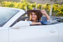Cowboymädchenfahrer im weißen Kabriolett Stockfotografie