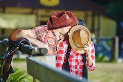 Cowboypaare, die einen Kerl und ein Mädchen in den Cowboyhüten küssen stockfotos