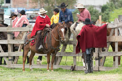Cowboys from the Andes sitting on the fence. June 3, 2017 Machachi, Ecuador: cowboys from the Andes sitting on the fence in the morning in the high altitude town stock image