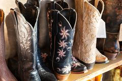 Cowboys boots on a shelf in a store, aligned. Cowboys leather boots on a shelf in a store, aligned royalty free stock photography
