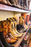 Cowboys boots on a shelf in a store, aligned. Ornate Cowboys boots on a shelf in a store, aligned. Vertical stock photography