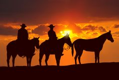 Cowboys and horses under sunset stock images