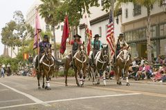 Cowboys marching with American and California flags displayed during opening day parade at annual Old Spanish Days Fiesta held eve Royalty Free Stock Photography