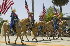 Cowboys marching with American Flags displayed during opening day parade down State Street, Santa Barbara, CA, Old Spanish Days Fi Stock Images