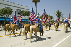 Cowboys marching with American Flags displayed during opening day parade down State Street, Santa Barbara, CA, Old Spanish Days Fi Stock Photo