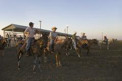 Cowboys no por do sol no rodeio de PRCA fotografia de stock